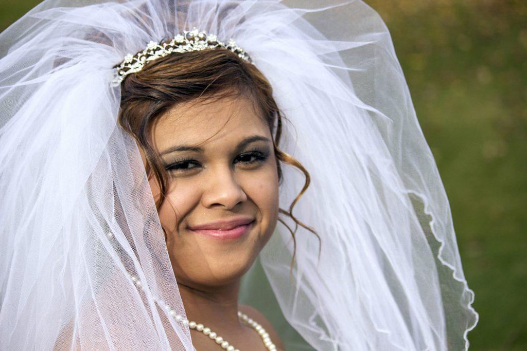 Bride smiles in her wedding dress before ceremony.