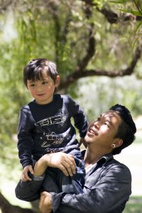Father holds his young son on his shoulders at an outdoor park.