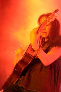 Gabriela gets lost in the guitar on stage of Rodrigo y Gabriela.